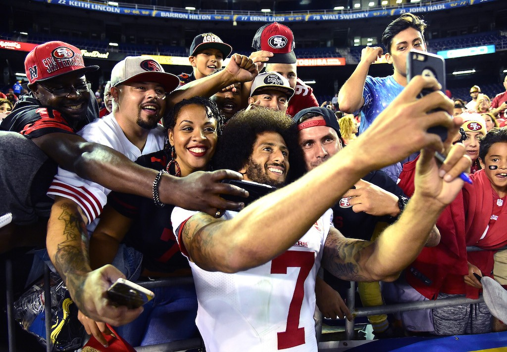 Colin Kaepernick poses for photos with fans.
