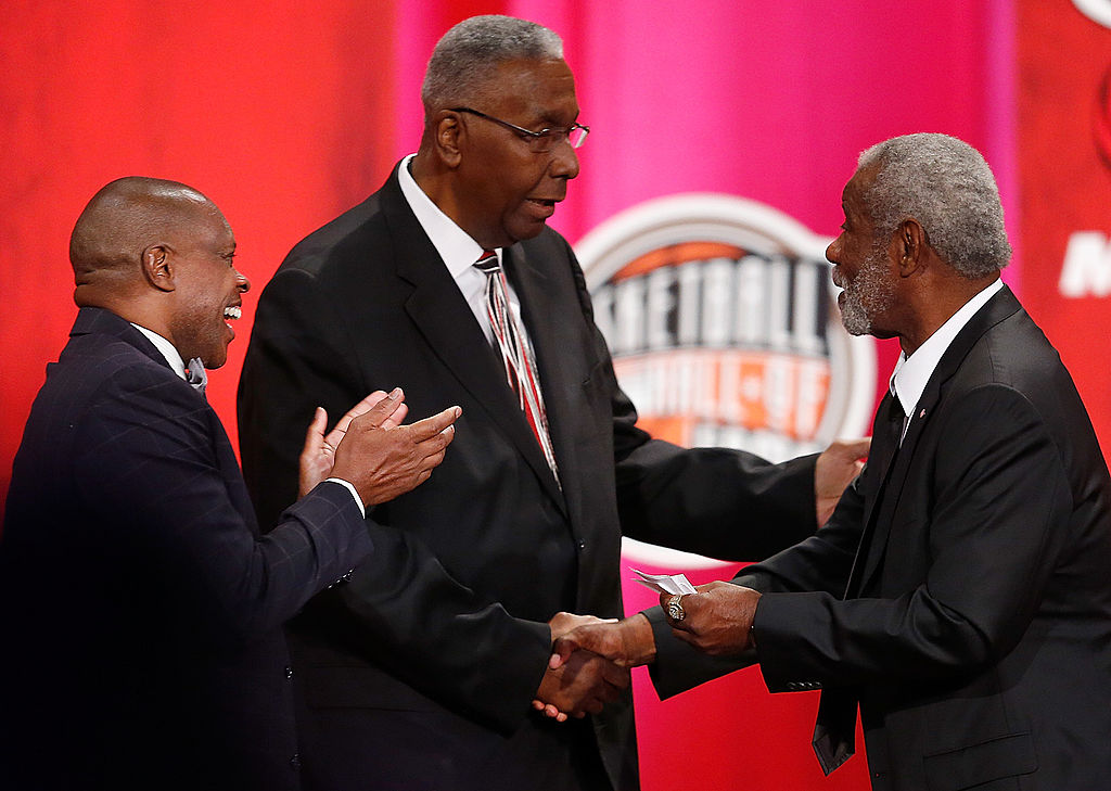 John Thompson and player Nate Archibald shake hands.
