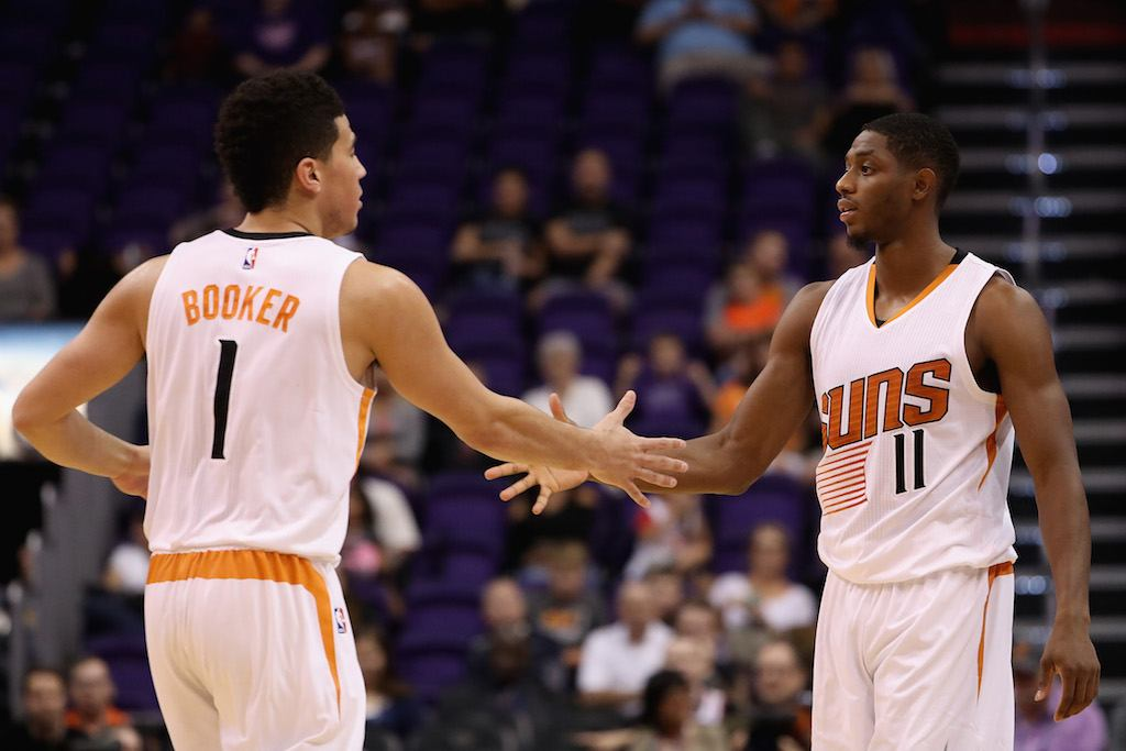Two members of the Phoenix Suns shake hands during a game.