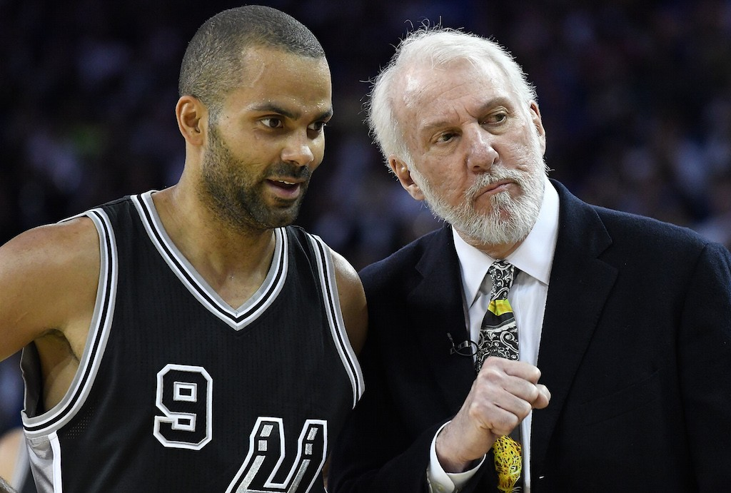 Gregg Popovich (R) chats with Tony Parker.