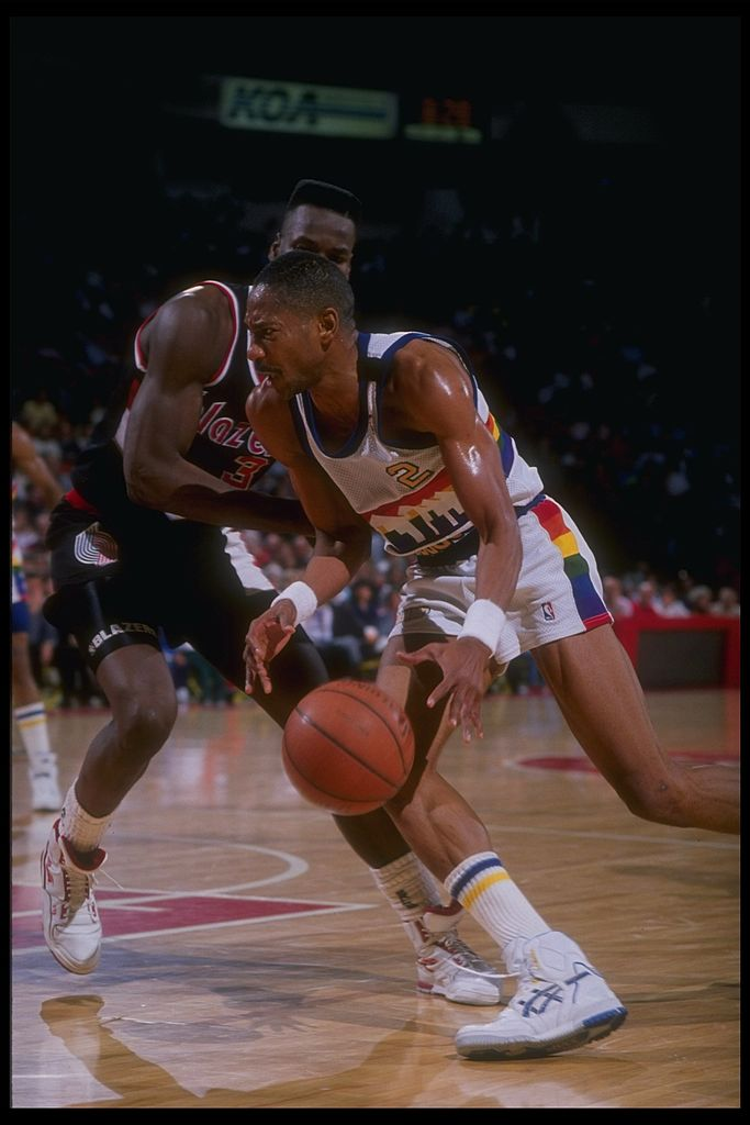 Guard Alex English of the Denver Nuggets dribbles past a defender.