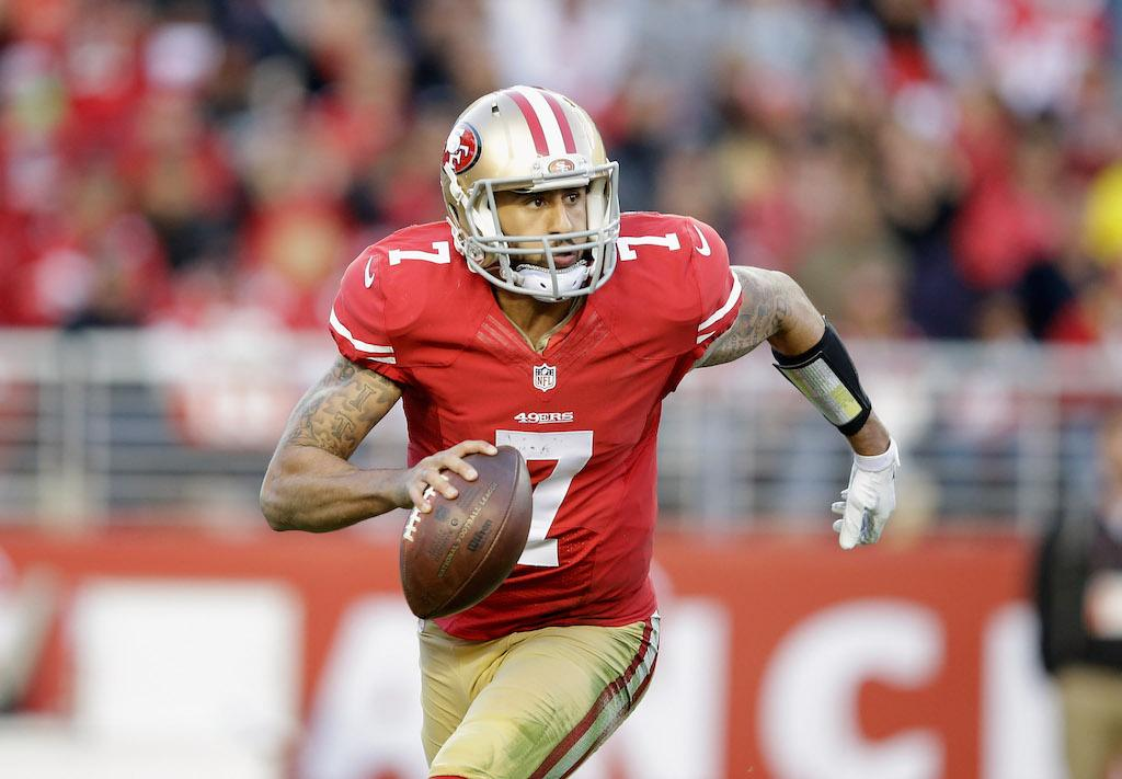 The 49ers' Colin Kaepernick grips the ball and runs downfield.