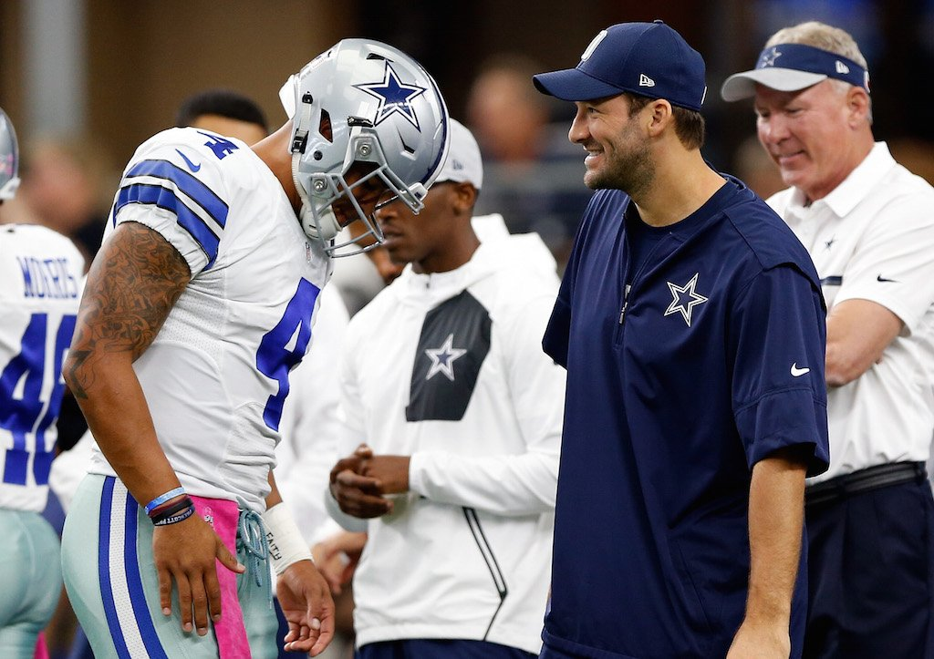 Tony Romo laughs with Dak Prescott on the sideline.