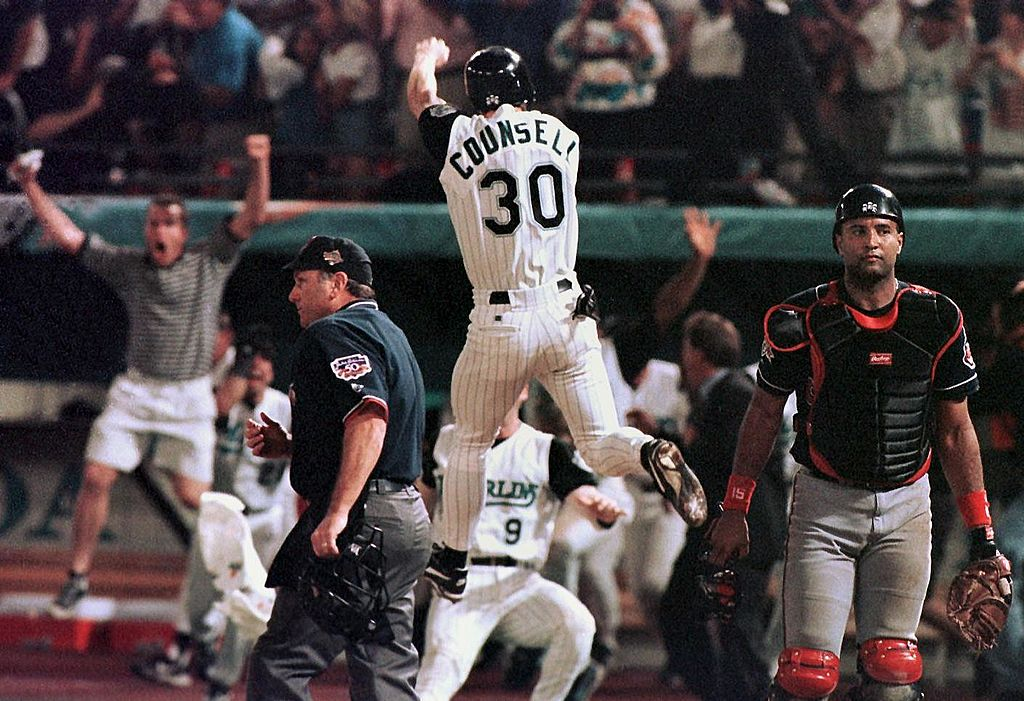 Florida Marlins player Craig Counsell jumps in the air after crossing the plate with the winning run