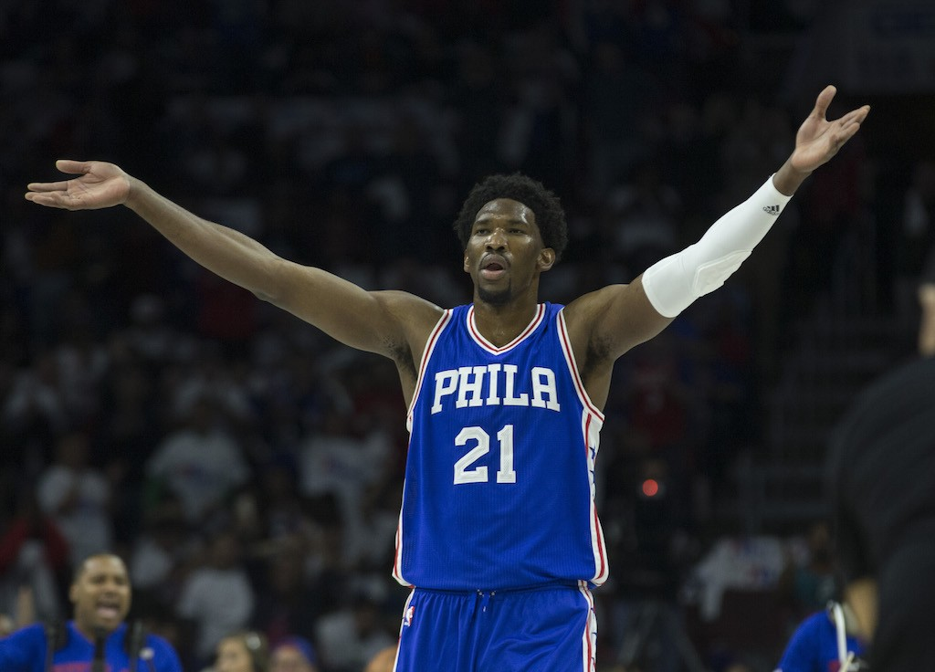 Joel Embiid raises his hands to pump up the crowd.