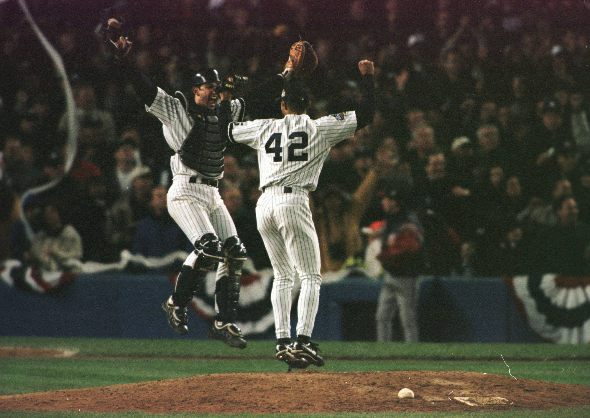Catcher Jorge Posada of the New York Yankees leaps into the air with Mariano Rivera