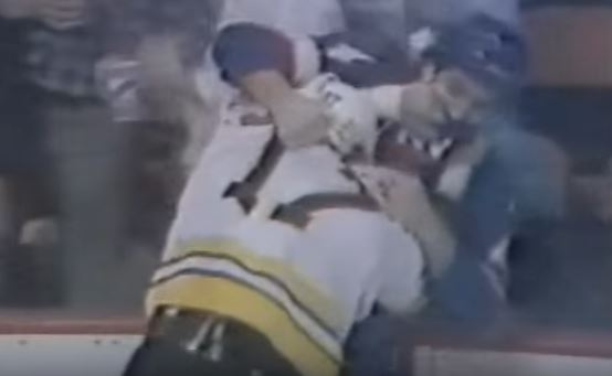 Two members from the Boston Bruins and New York Islanders fighting during a game