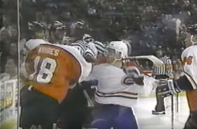 Members of opposing hockey teams fighting up against the glass during a game.