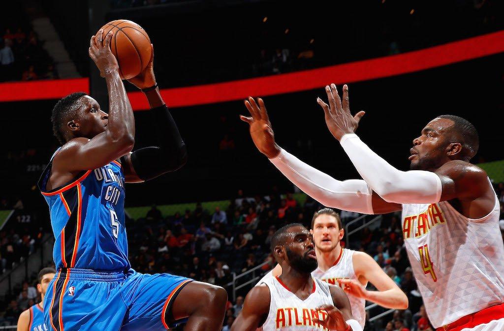 Paul Millsap (R) jumps to block Oklahoma City Thunder's Victor Oladipo