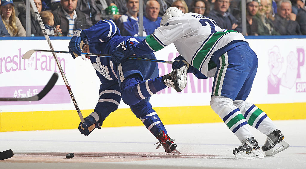 Daniel Sedin of the Vancouver Canucks knocks down Nazem Kadri of the Toronto Maple Leafs | Claus Andersen/Getty Images