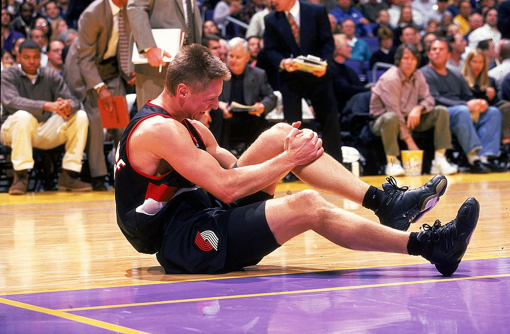 Detlef Schrempf of the Portland TrailBlazers sits on the court holding his knee