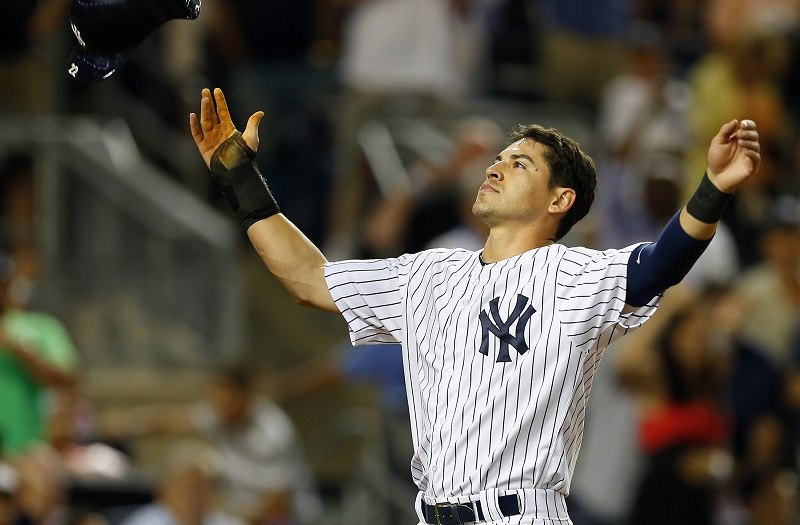 Jacoby Ellsbury of the New York Yankees reacts by throwing his helmet in the air after finding out that the run he scored on a stolen base and a two base error were nullified