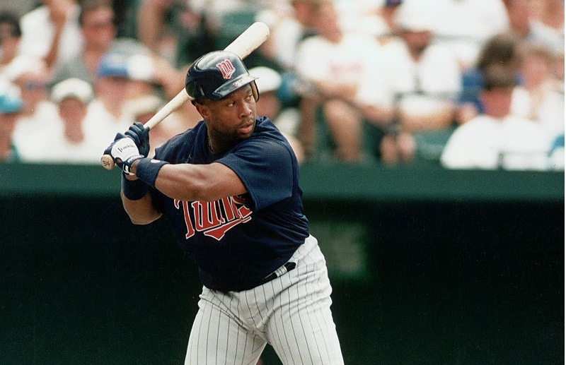 American professional baseball player Kirby Puckett (1960 - 2006) of the Minnesota Twins begins to swing at a pitch during an away game, late 20th Century. Puckett played for the Twins from 1984 to 1996, the entirety of his professional career.