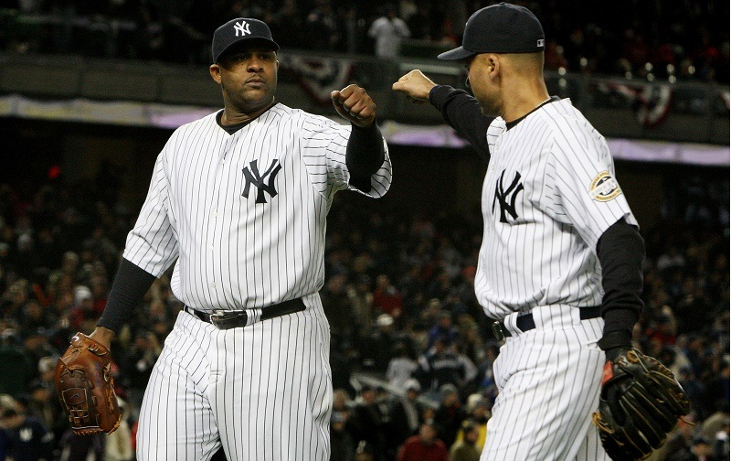 CC Sabathia (L) of the New York Yankees walks off the field and is congratulated by Derek Jeter during Game 1 of the 2009 ALCS