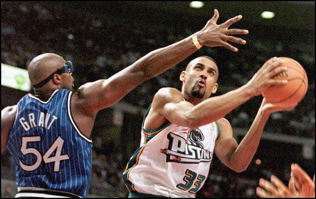 The Detroit Pistons' Grant Hill (R) drives past the Orlando Magic's Horace Grant.