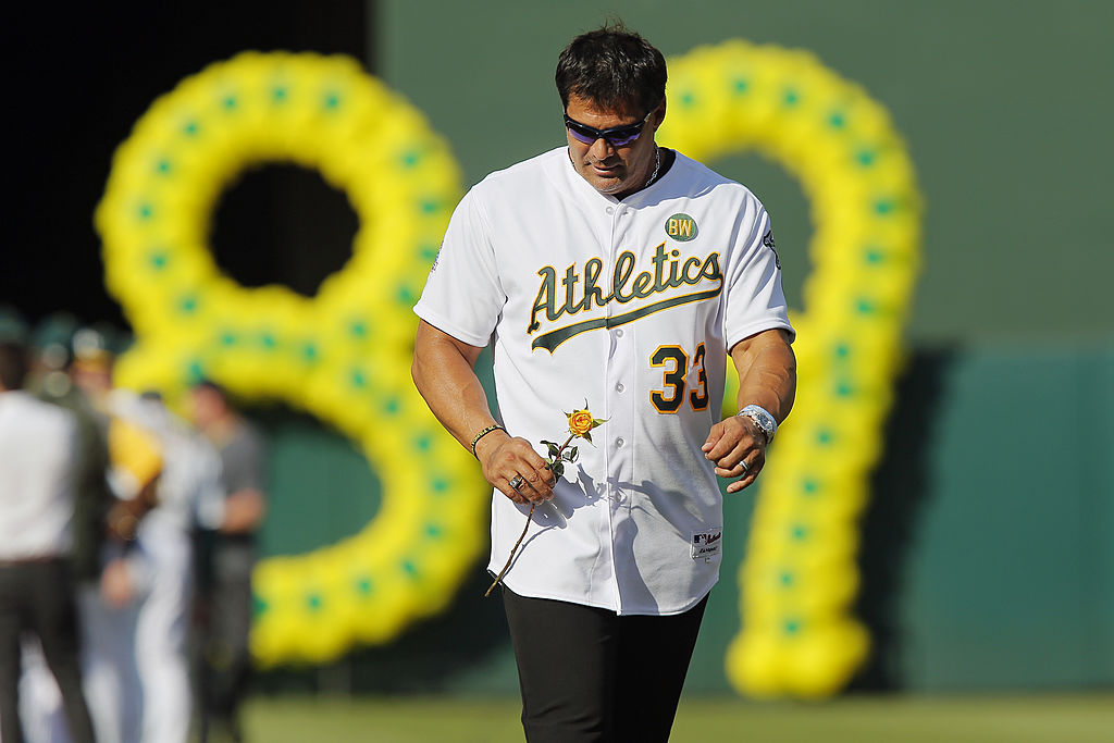 Jose Canseco carried a yellow rose while wearing an Oakland A's jersey