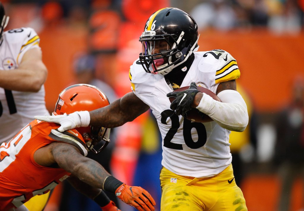 Le'Veon Bell pushes past a defender.