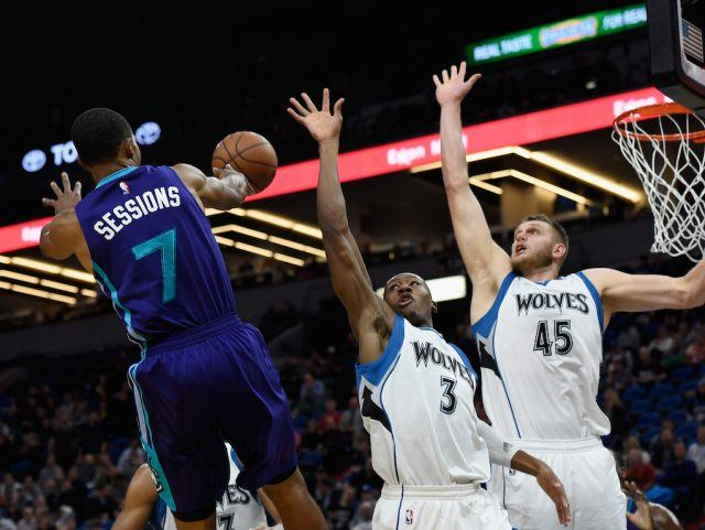 Two Timberwolves players attempt to block the Charlotte Hornets' Ramon Sessions