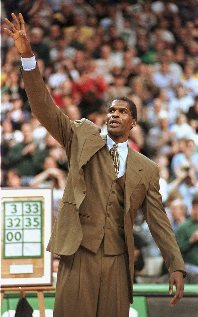 Former Boston Celtics player Robert Parish waves from the sideline.