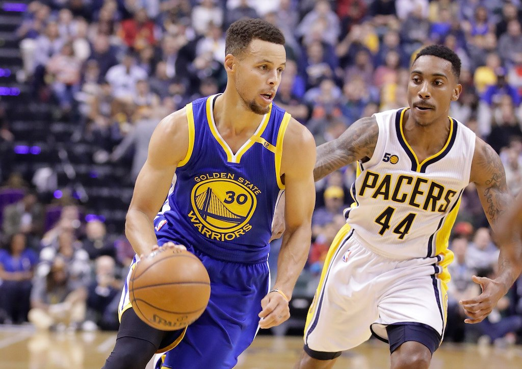 Stephen Curry drives the ball down the court past an opposing team member