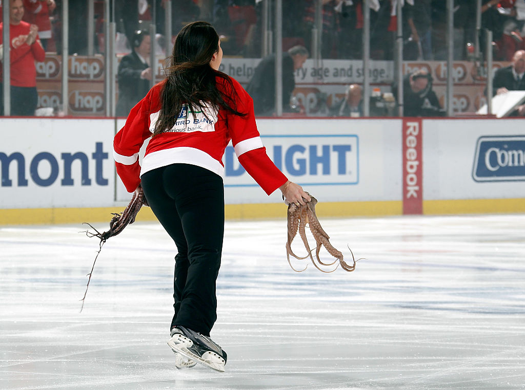 A member of the Detroit Red Wings ice crew remove two octopus
