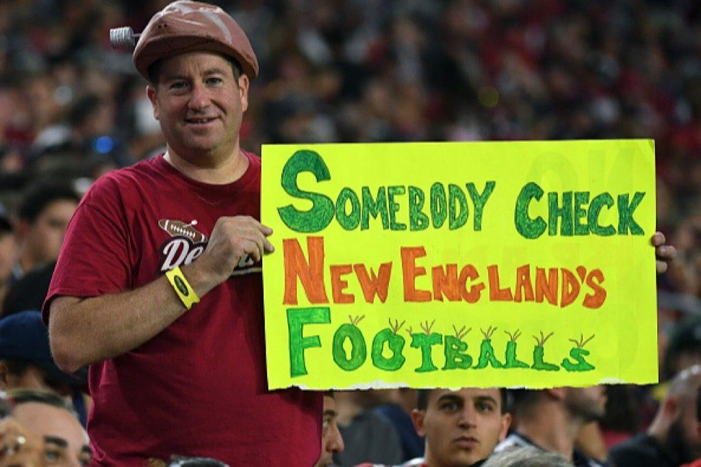 An Arizona Cardinals fan wearing a deflated football hat holds up a sign referencing Deflategate during the team's game against the New England Patriots | Ethan Miller/Getty Images