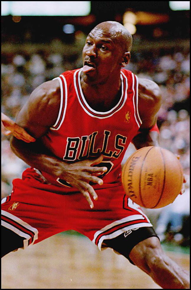 Chicago Bull Michael Jordon makes a face while guarding the ball against an opponent.