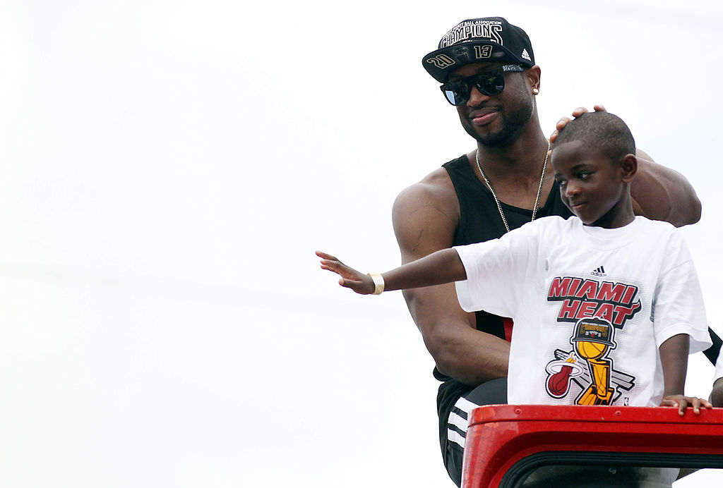 Guard Dwyane Wade of the Miami Heat rides a bus with his son during the championship victory parade on the streets of Miami | Marc Serota/Getty Images