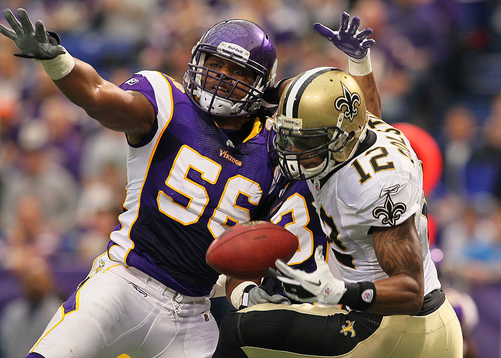 E.J. Henderson of the Minnesota Vikings attempts to disrupt the pass to Marques Colston of the New Orleans Saints.