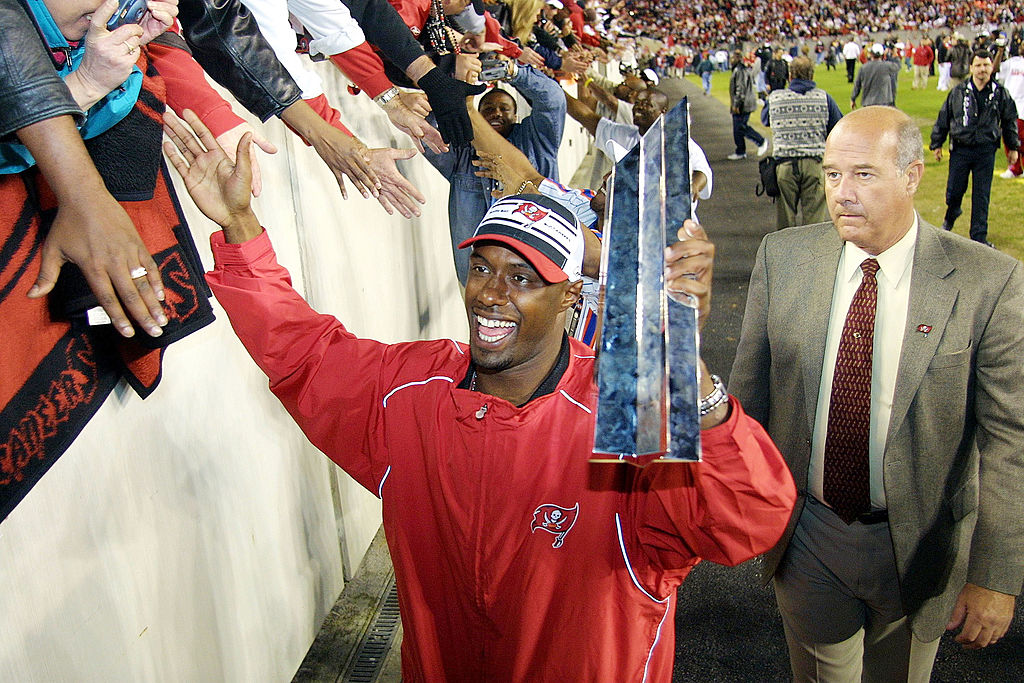 Tampa Bay Buccaneer Dexter Jackson high-fives fans while holding his Super Bowl MVP trophy.
