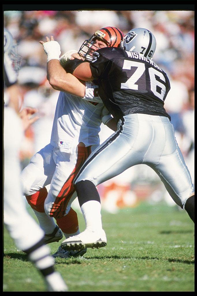 Offensive linemen Steve Wisniewski of the Los Angeles Raiders blocks defensive linemen Tim Krumrie of the Cincinnati Bengals.