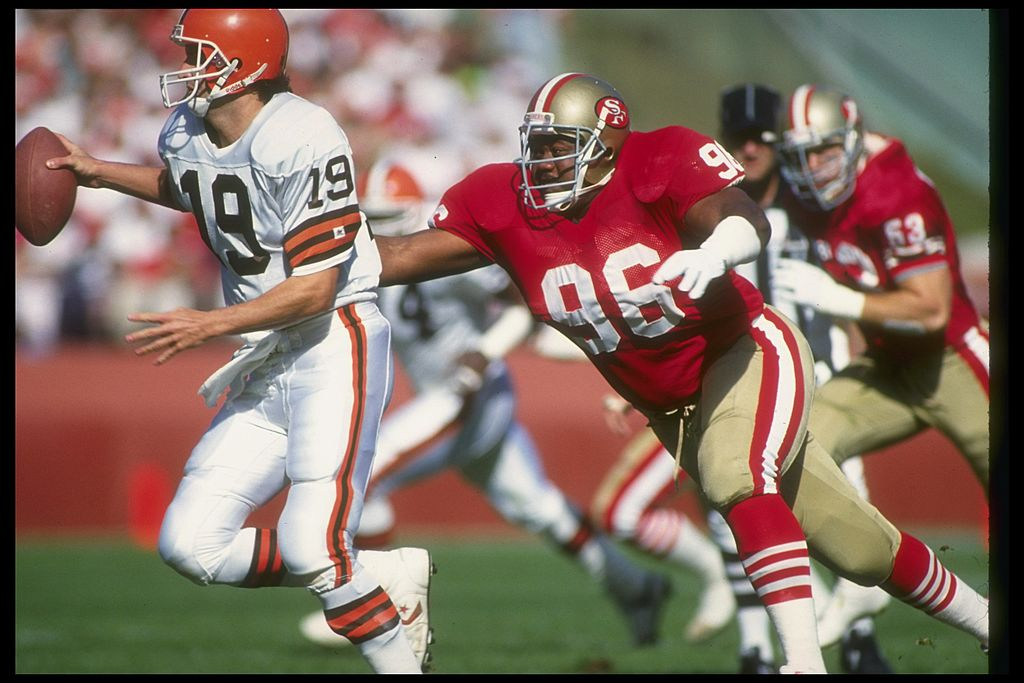 Quarterback Bernie Kosar of the Cleveland Browns scrambles to avoid a San Francisco 49ers player