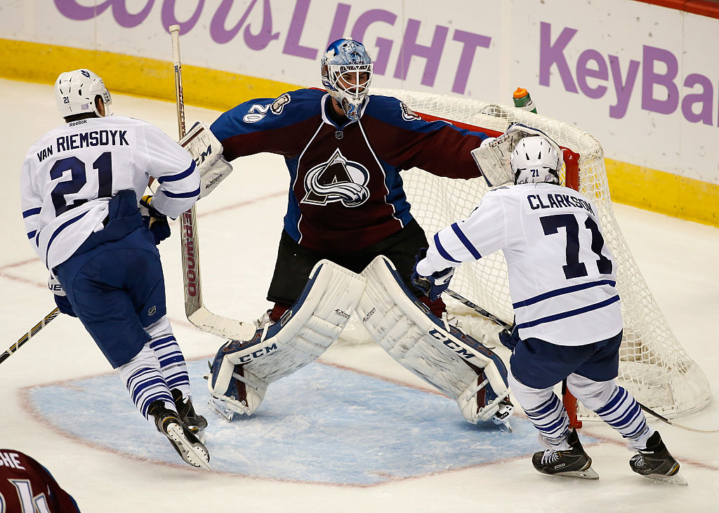 Goalie Reto Berra of the Colorado Avalanche defends the goal against James van Riemsdyk and David Clarkson of the Toronto Maple Leafs Leafs.