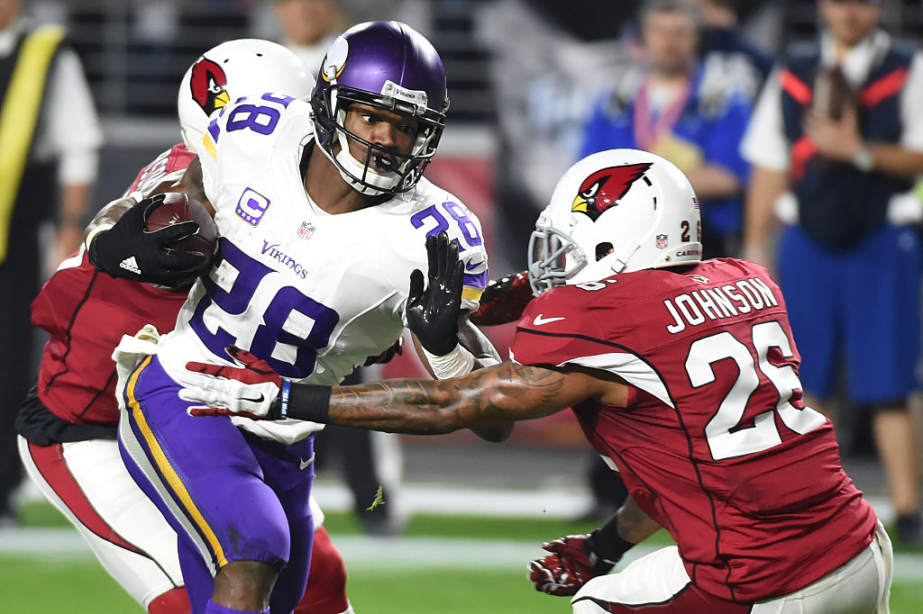 Running back Adrian Peterson of the Minnesota Vikings rushes the football against free safety Rashad Johnson of the Arizona Cardinals.