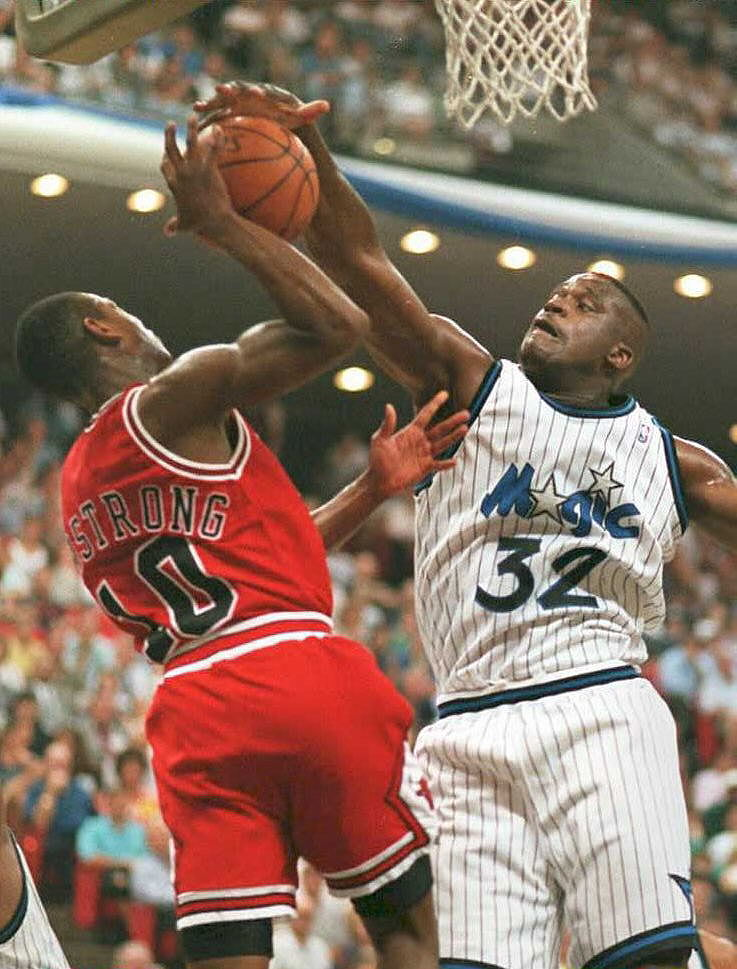 Shaquille O'Neal of the Orlando Magic stuffs BJ Armstrong of the Chicago Bulls | TONY RANZE/AFP/Getty Images)