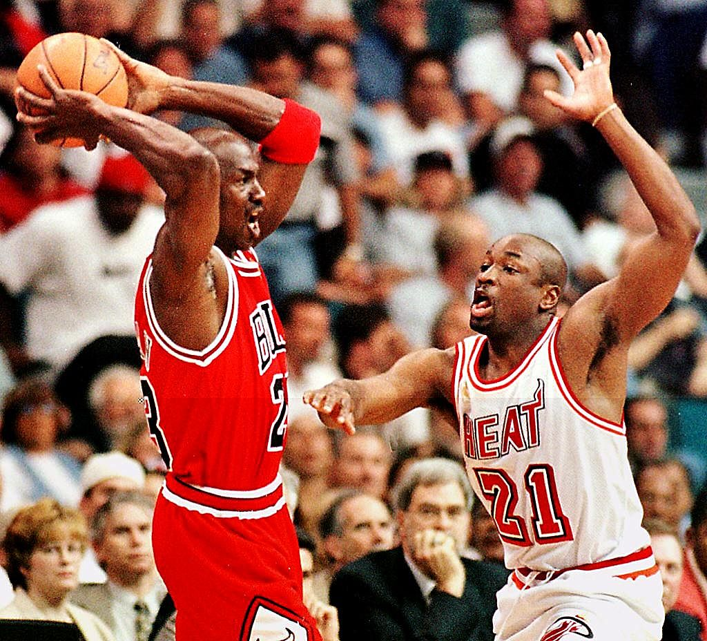 Michael Jordan of the Chicago Bulls handles the ball as Voshon Lenard of the Miami Heat struggles to keep him covered.