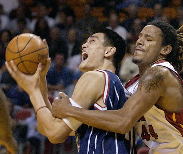 Miami Heat center Brian Grant fouls Houston Rockets' center Yao Ming | RHONA WISE/AFP/Getty Images