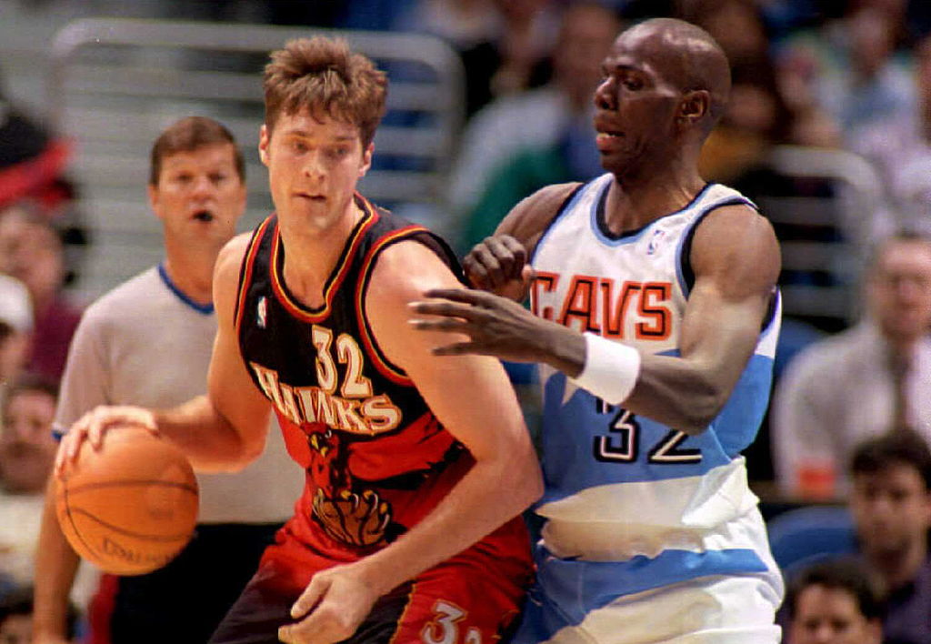 Atlanta Hawks center Christian Laettner drives for the basket around Cleveland Cavaliers forward Tyrone Hill.