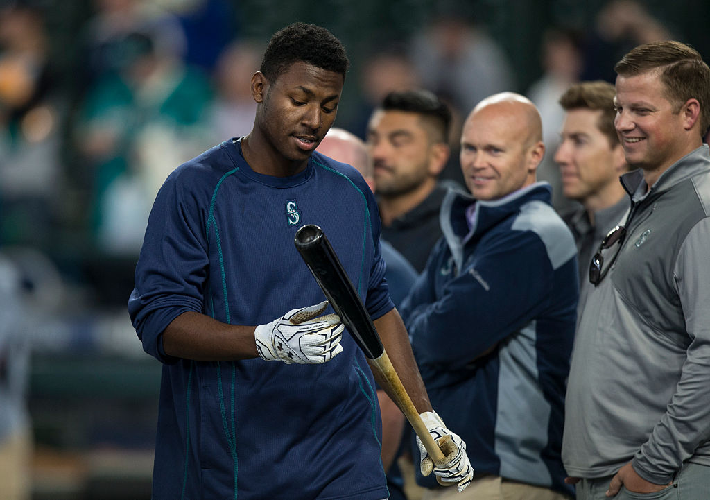 Seattle Mariners 2016 first round draft pick Kyle Lewis walks past scout during batting practice