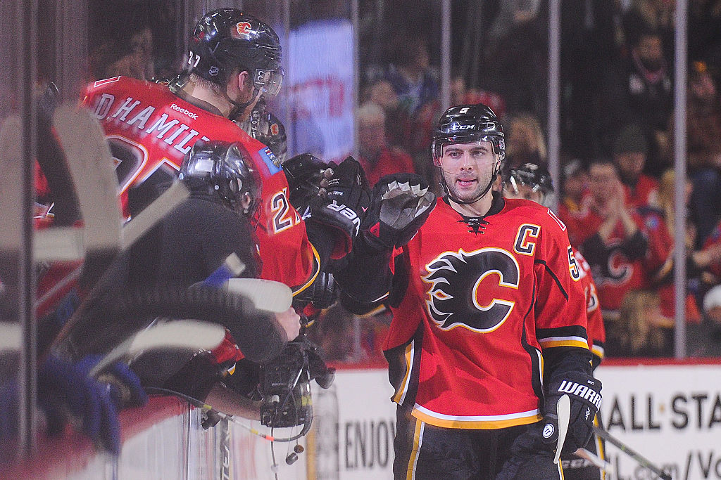 Mark Giordano of the Calgary Flames celebrates with his teammates after scoring his team's third goal.