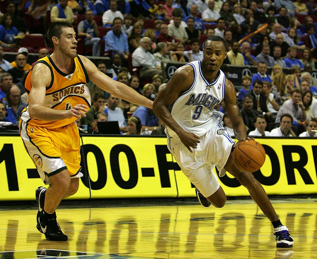 Rashard Lewis of the Orlando Magic drives past Nick Collison of the Seattle SuperSonics.