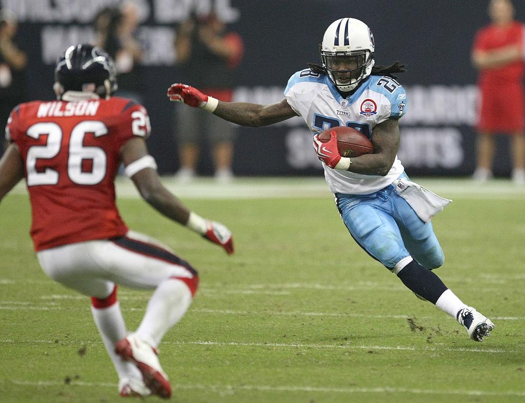 Eugene Wilson of the Texans goes at running back Chris Johnson | Stephen Dunn/Getty Images