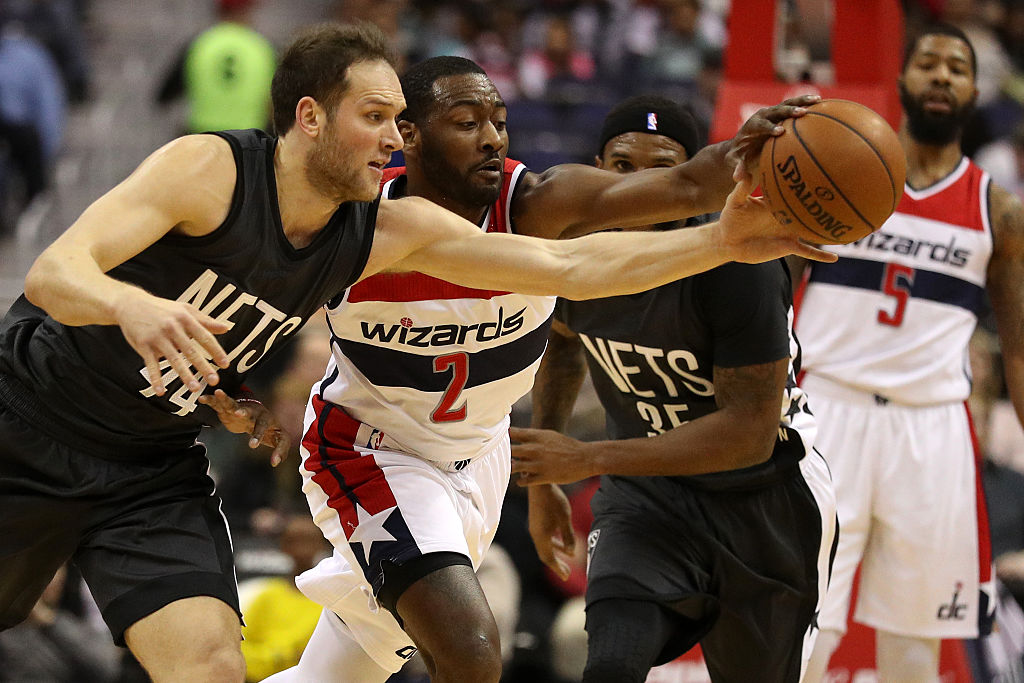 John Wall of the Washington Wizards tries to take control of the ball during a game.