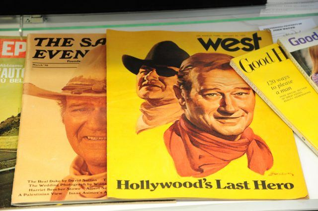 John Wayne's face appears on the covers of many magazines.