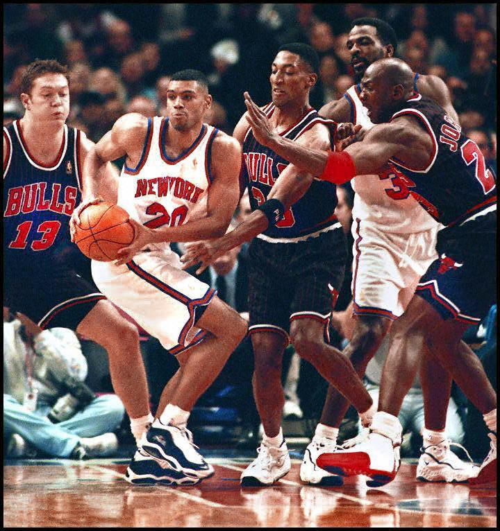 Michael Jordan, and other members of the Chicago Bulls, attempt to steal the ball from Charles Oakley of the Knicks