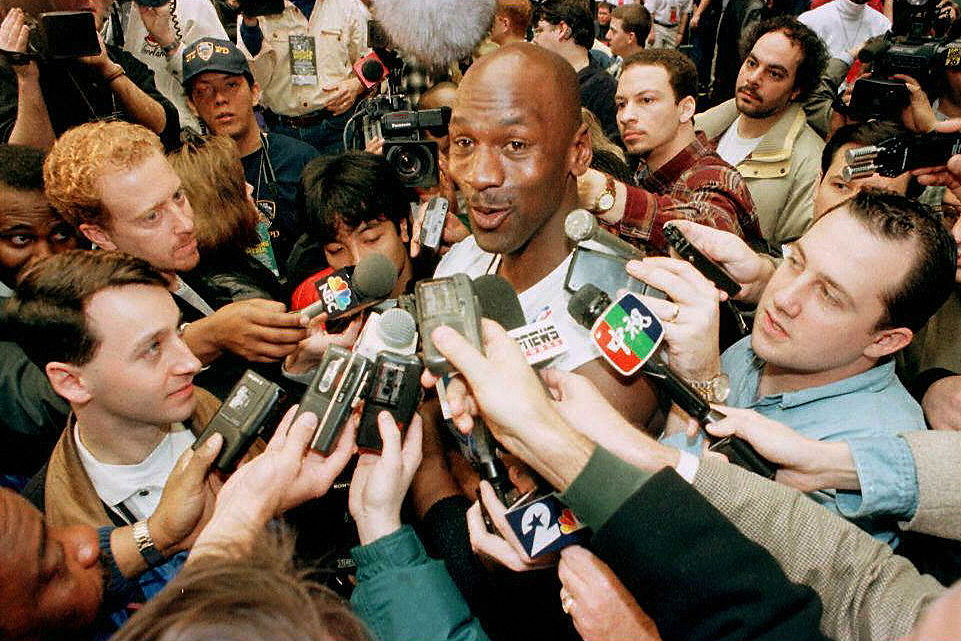 Michael Jordan surrounded by members of the media following a game