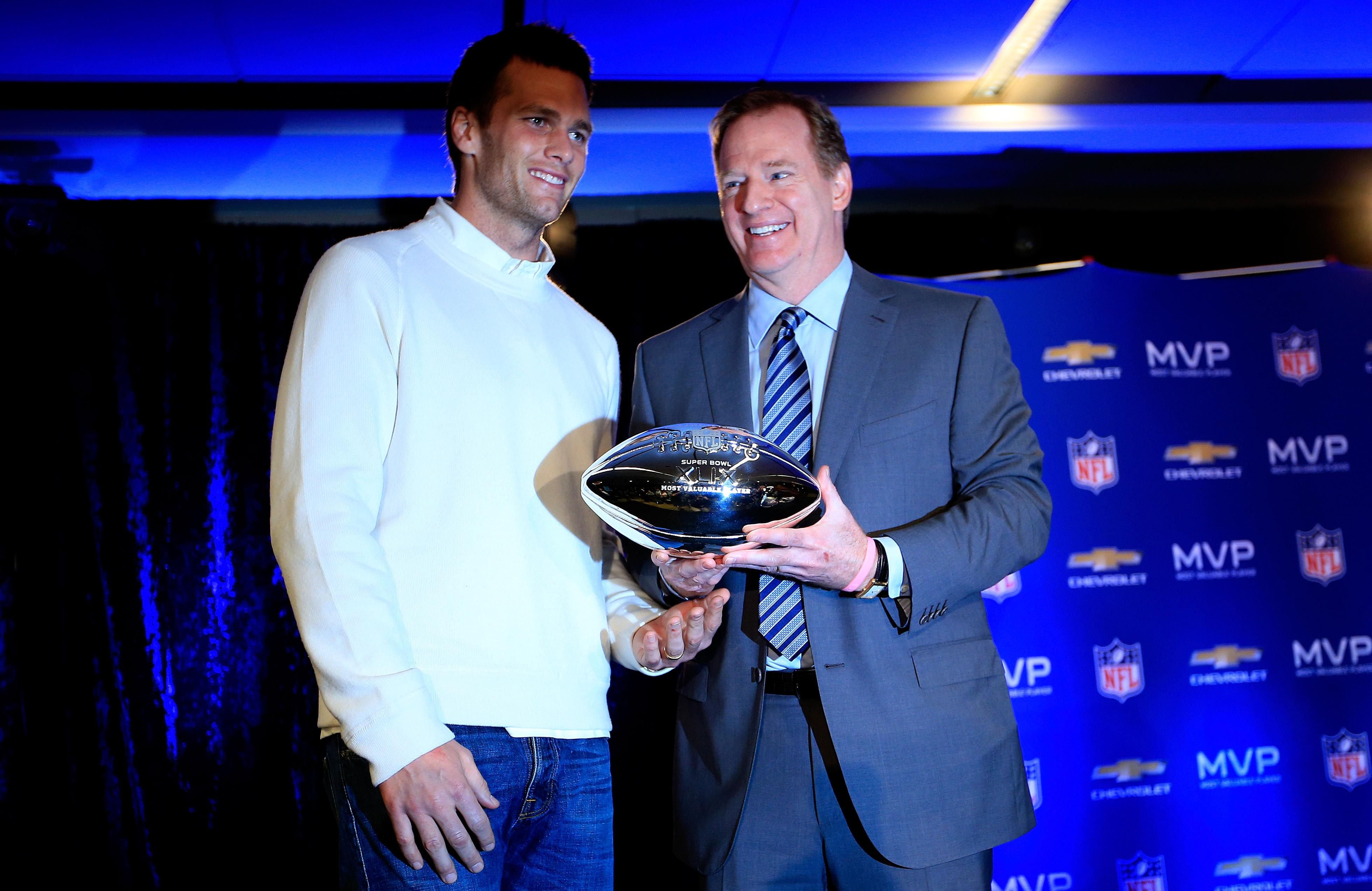 Tom Brady and Roger Goodell stand together on stage.