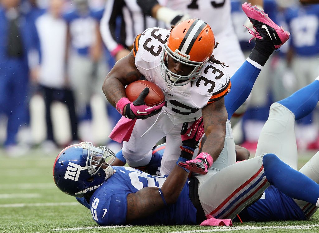 Trent Richardson holds tight to the ball as he falls to the ground.