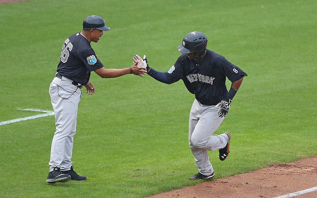 Miguel Andujar of the New York Yankees celebrates with third base coach Tony Pena after hitting a two run home run