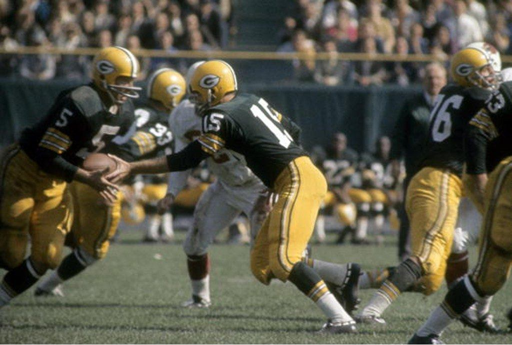 Running back Paul Hornung of the Green Bay Packers takes the hand off from quarterback Bart Starr.